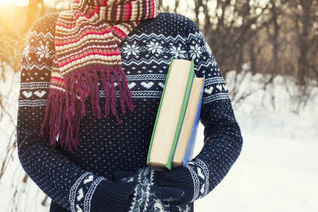 50629836 - girl in a wool sweater keeps old books.